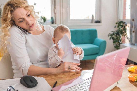 Gestresste Frau hält Baby, telefoniert und arbeitet am Laptop