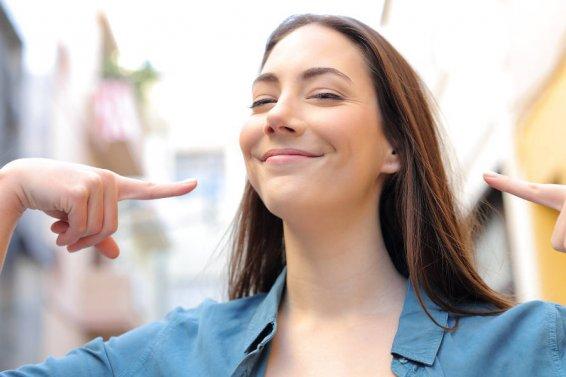 Frau zeigt stolz und zufrieden auf sich selber